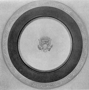 Service Plate from Wilson Service: The borders are of etched gold and the rim of cobalt blue. The President's seal in the center is of raised paste and gold.