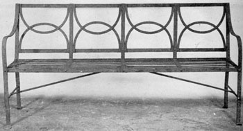 A Sheraton Garden Bench in Wrought Iron: The lines and design in this piece were clearly inspired by those of the sofas by Thomas Sheraton.