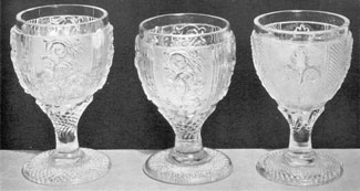 Typical Sandwich Goblets of Lacy Design: Goblets A and B are of the same design but B has a shorter and stockier stem, due to method used in casting bowls and footing separately, and then joining them when still hot. Goblet B has the pinkish tint to be observed in many Sandwich lacy objects.