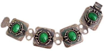 Hammered silver was a favorite of Arts & Crafts jewelers. This silver bracelet is offset by brilliant green enamel centers.