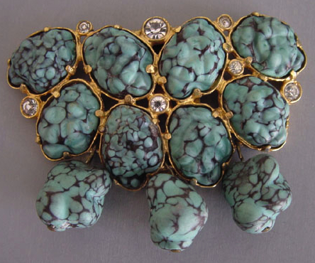 Aqua glass nuggets resembling turquoise dominate this circa-1940 gold-tone dress clip.