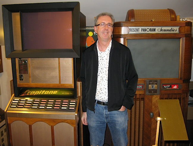 Scopitone film collector Bob Orlowsky poses between a U.S. Scopitone (left) and a Panoram (right), both owned by Dick Hack.