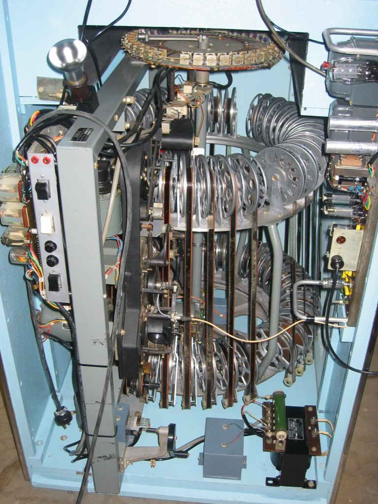 The inside workings of a Scopitone machine show how the films were mounted on a carousel, which rotated until the consumer's selection was aligned with the projector.