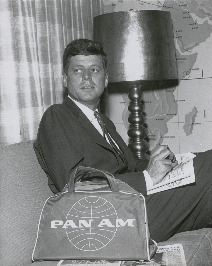 Senator John F. Kennedy awaits a flight in the Clipper Club, 1959. Lettering on bags made between 1957 and '62 extended beyond the edge of the globe.