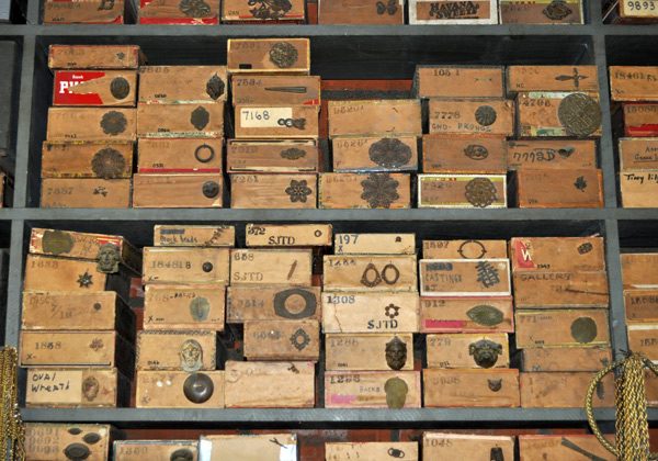 Jewelry parts are still stored in cigar boxes, as they were in Joseff's time. The writing on the boxes has yet to be decoded, but Tina and Michele know the numbers have to do with the dealer Joseff bought his parts from and the price he paid. Click image for a larger view.