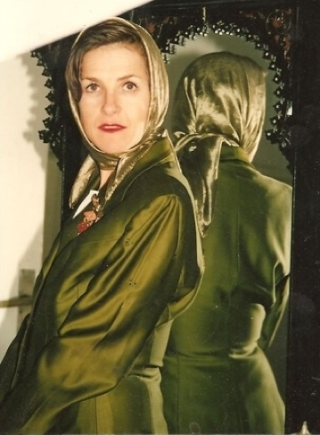 Salamon does a feminine Grace Kelly look in Egypt, with a '40s green silk jacket, a '40s silk head scarf, and a three-tier moonstone brooch.