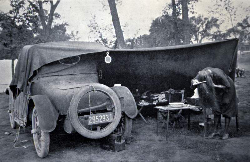 A car camper does a little rustic grooming in Rocky Mountain National Park during the 1920s.