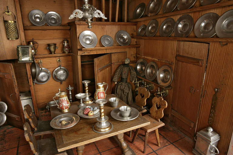 Fine silver, tiny beer steins, and wood furniture in the Nuremberg doll house pictured in full above. From Victoria and Albert Museum collection.