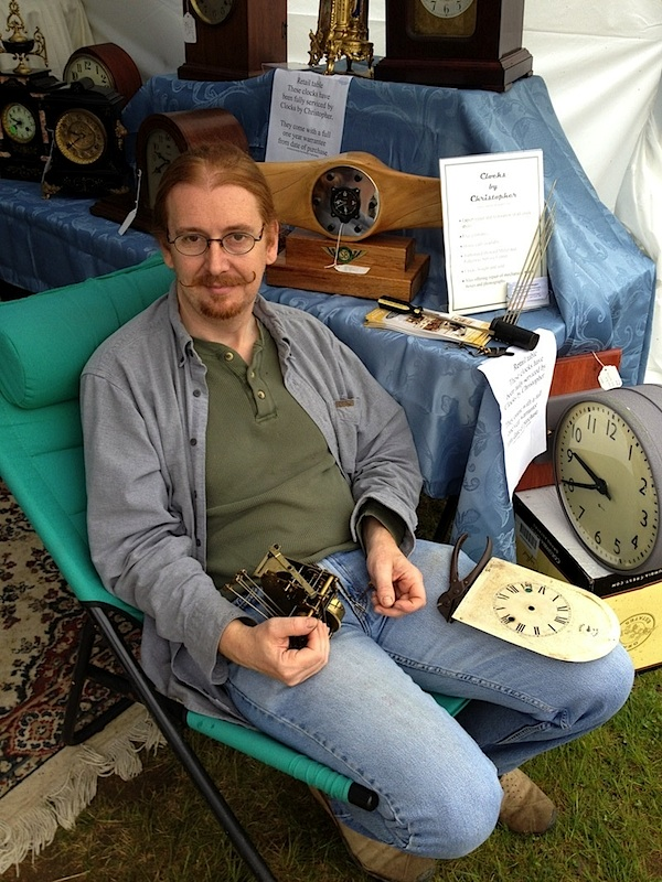Christopher, who restores antique timepieces, is shown manning his ClocksByChristopher.com booth at the May Brimfield. Photo by Ben Marks.