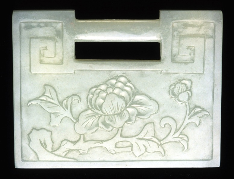 Carved nephrite lock pendants such as this one from the 19th century were given to infant boys to protect them. The peony is a symbol of wealth.