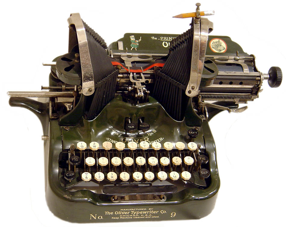 A 1910s Oliver typewriter with its peculiar U-shaped typebars, like this one in Polt's collection, sits on a shelf in Hanks' Playtone offices. Via The Classic Typewriter Page.