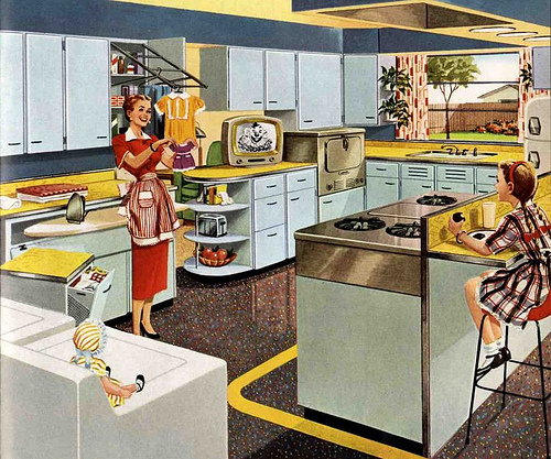 This 1953 advertisement for KitchenMaid cabinets shows a housewife delighting in the modern marvels of her kitchen. Via RetroRenovation.com.