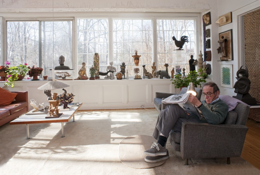 "Harper reads the paper in his living room, surrounded by his own artworks. Photo by Leslie Williamson, from ""Irving Harper Works in Paper."""