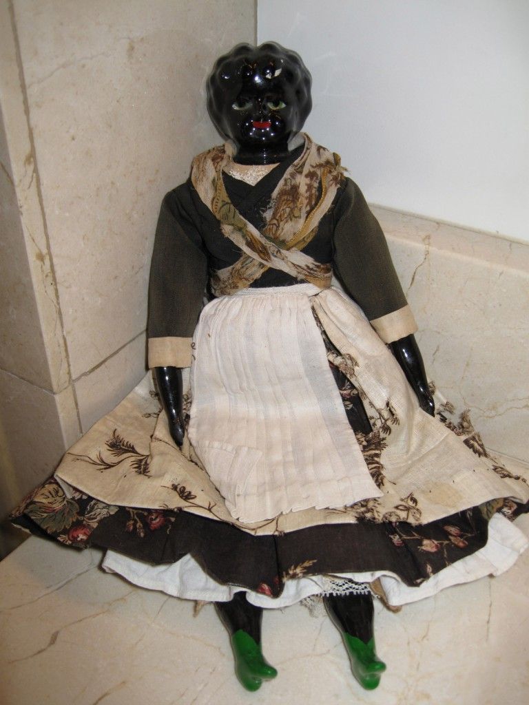 This antique European porcelain doll depicts a black woman with green eyes.