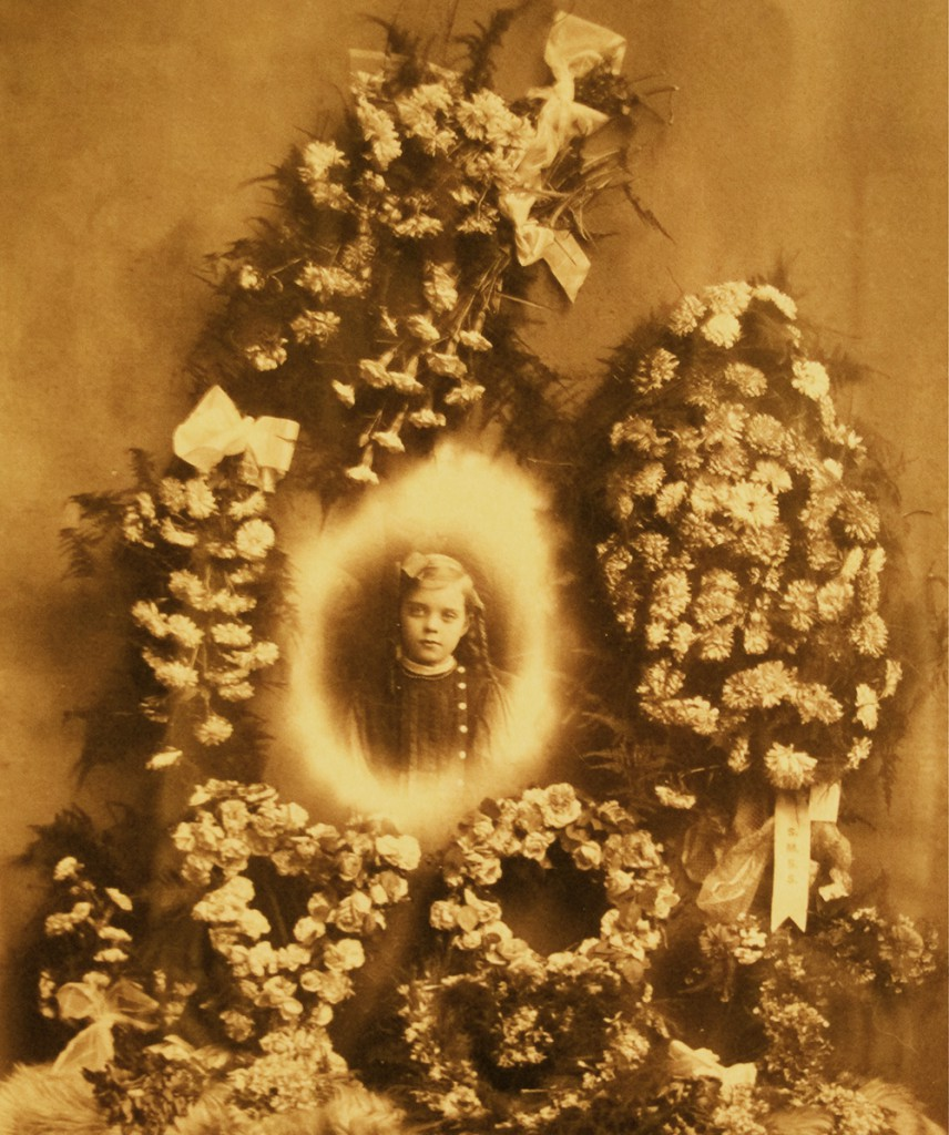 Early examples of trick photography were used to create funeral tableaus, like image of a young girl collaged onto floral arrangements, circa early 1900s.