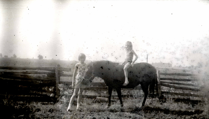 Two girls posing with a horse that appears to have only three legs. Courtesy Chris Hughes.