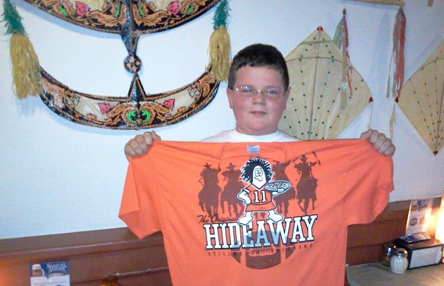 "Nash, celebrating his 14th birthday in the Stillwater restaurant in 2011, holds up a Hideaway Pizza T-shirt with an Oklahoma State Cowboys theme. The wall behind him features a ""wau bulan"" moon kite from Malaysia and two ""pakpao"" female kites from Thailand. Via the original Hideaway Pizza Facebook page."