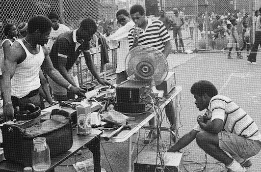 Top: DJ Kool Herc deejays in NYC in 1999. Photo by Mika Väisänen, via WikiCommons. Above: Kool Herc and the Herculoids put on a Bronx party in the 1970s. Via The Flog.