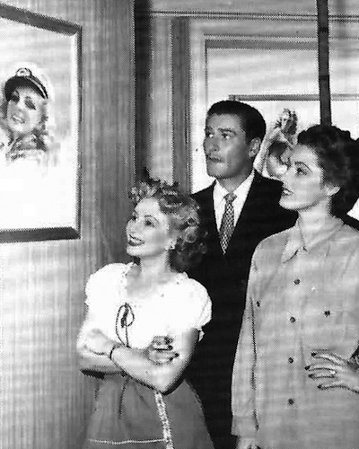 "Mozert shows her work to Errol Flynn and Eleanor Parker, the stars of 1946's ""Never Say Goodbye."" The artist served as a consultant and provided the art for the film, which features Flynn as a George Petty-type pin-up painter. Via ""Tease!""#3."