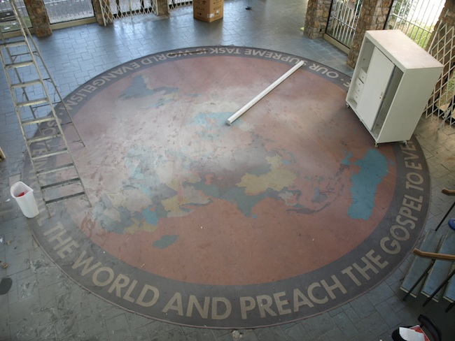 "The large vinyl rug at The World Museum read, ""Go ye into all the world and preach the Gospel to every creature. Our supreme task is world evangelism."" Pictured before demolition. (Photo by Rex Brown, via OklahomaModern.us)"