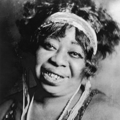 "Top: Cabaret singer and pianist Gladys Bentley, who performed in a tuxedo, drew a crowd to the Clam House in Harlem in the 1920s. (Postcard image via QueerMusicHeritage.us) Above: Ma Rainey, ""The Mother of the Blues,"" sang about pursuing women on a handful of tunes. (1917 image via WikiCommons)"