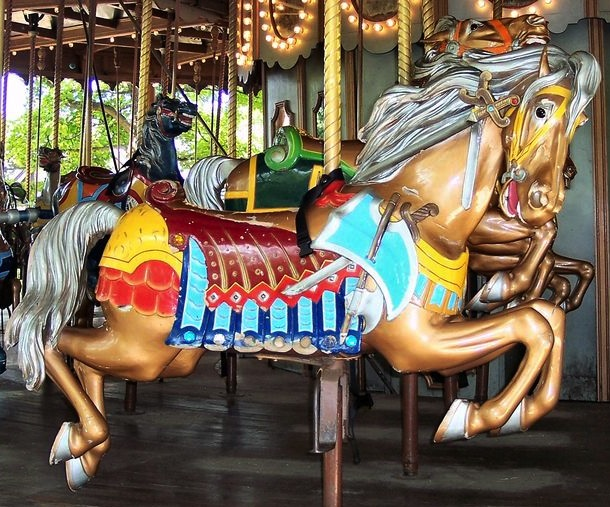"Top: Outside-row animals, like this stander on the 1914 Herschell-Spillman carousel at Golden Gate Park, have the more elaborate carvings than the inside-row animals, especially on the ""romance side."" (© Aaron Shepard, via carousels.org) Above: This outside-row jumper, a war horse, is a part of the 1915 Grand Ole Carousel at Six Flags St. Louis in Eureka, Missouri, designed by Philadelphia Toboggan Company. (© Bette Sue Gray, both photos via carousels.org)"