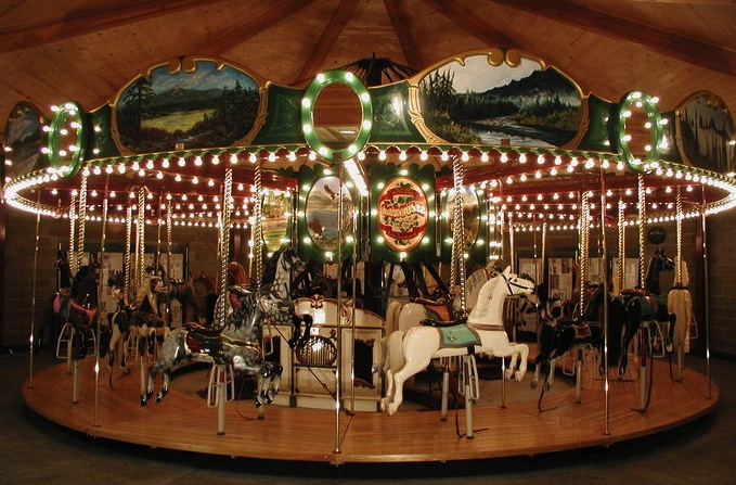 This Armitage-Herschell carousel, circa 1895-1900, was made with uniform horses for easier packing and transporting, but the rounding boards at top were still hand-painted with landscapes. (© Merry-go-round Friends, by Tom Craig, via carousels.org)