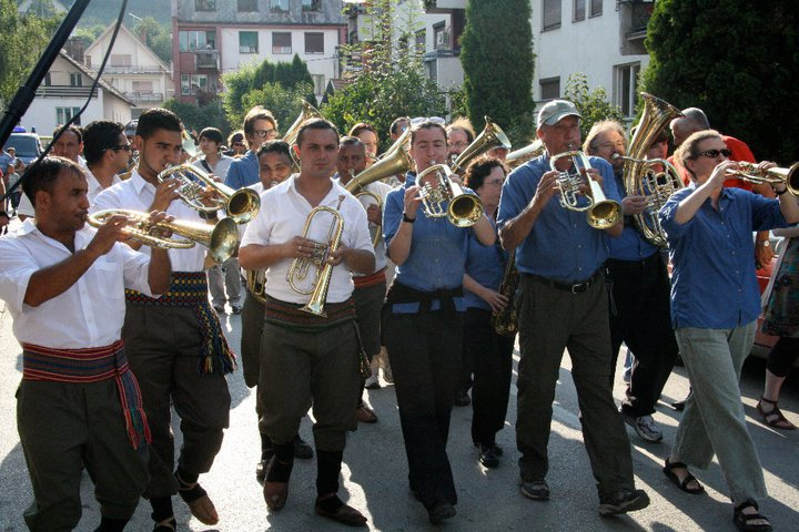 "Top: Brass bands play anywhere and everywhere during the Guča Trumpet Festival, and the crowds love it. (Still from ""Brasslands"" courtesy of the Meerkat Media Collective) Above: Demiran Ćerimović and his orchestra play with the American band Zlatne Uste in the streets. (Via the ""Brasslands"" Facebook page)"
