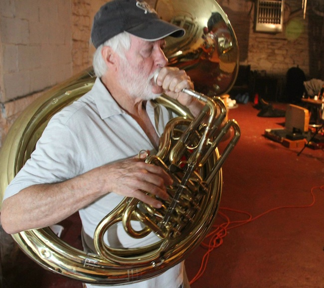 """Zlatne Uste member Emerson Hawley plays a helicon in a New York practice space. He uses his body to point the horn's bell, which determines how loud it will sound to the crowd. (Via the """"Brasslands"""" Facebook page)"""