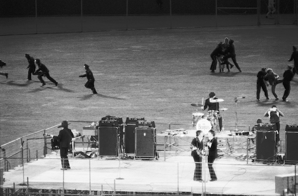 Police clear the field of fans as The Beatles perform in Candlestick Park, San Francisco, California, August 29, 1966. Photo: Bettmann/CORBIS.