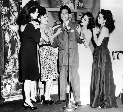 "Larry Ching, often referred to as the ""Chinese Frank Sinatra,"" sings to adoring chorus girls."