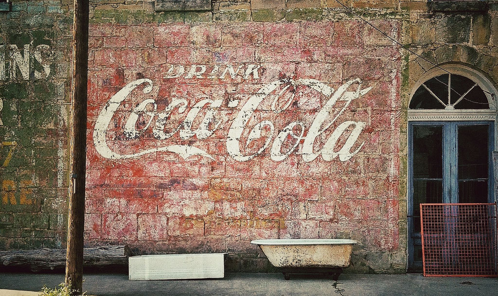 The familiar Coca-Cola logo, seen here on a hand-painted ghost sign in Gonzales, Texas, was originally designed using sign-lettering techniques. Photo by Molly Block.