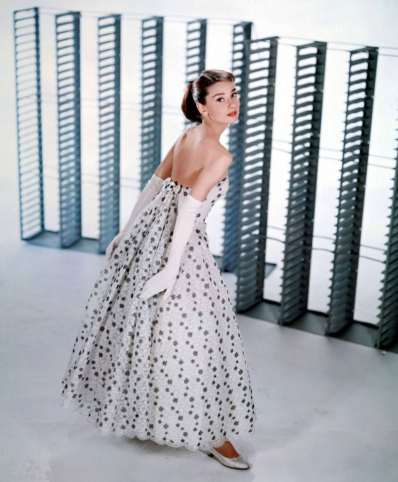 Audrey Hepburn works the hourglass-shaped, prom-queen look while in costume for Funny Face, circa 1956.