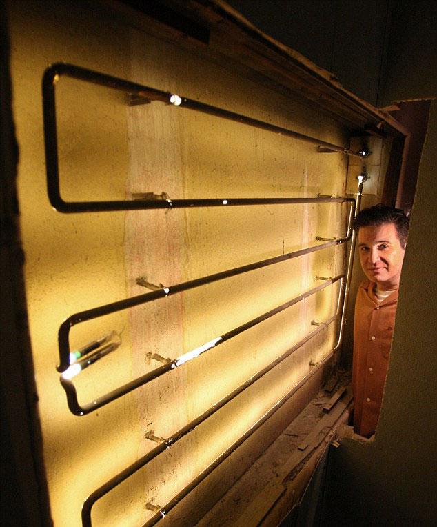 Andrew Meieran surveys the neon tubing hidden in a basement wall. Via latimes.com.