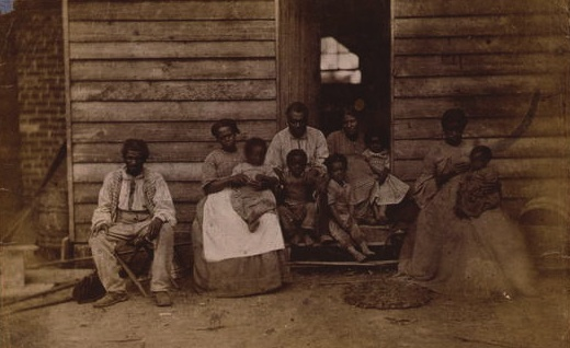 An enslaved African American family poses outside their cabin at the Gaines plantation in Virginia in the 1860s. (Photo by George Harper Houghton/Library of Congress)