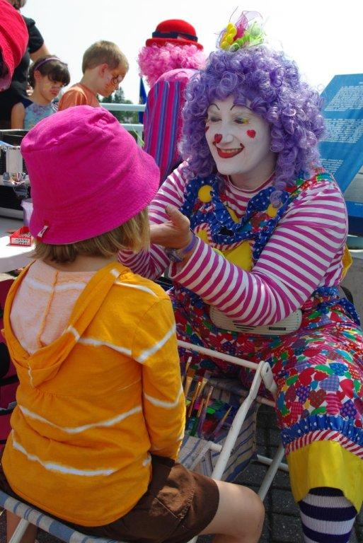 Deanna Hartmier, as Dee Dee the Clown, paints a little girl's face. Hartmier says she knows all the ingredients in her paints. (Courtesy of DeeDeeTheClown.com)