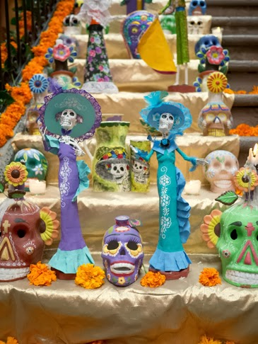 A Dia de los Muertos altar in Mexico City features marigolds, calaveras (sugar skulls), and calacas (skeleton figurines) of Catrina, the embodiment of elegance in death. (Photo by Joanna Ebenstein, via Morbid Anatomy)