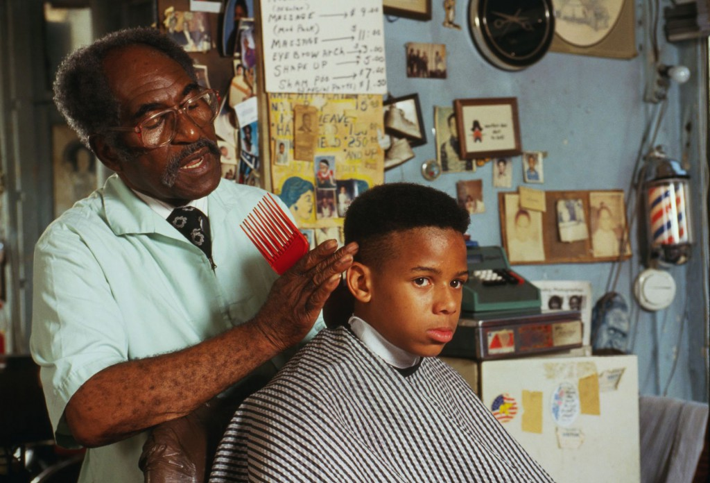Top: The Arthur Anderson Barber Shop in Mattoon, Illinois, which only served white customers, circa 1920. Above: Louis McDowell gives a young customer a high top fade in Paterson, New Jersey, in 1994. Via the Library of Congress.