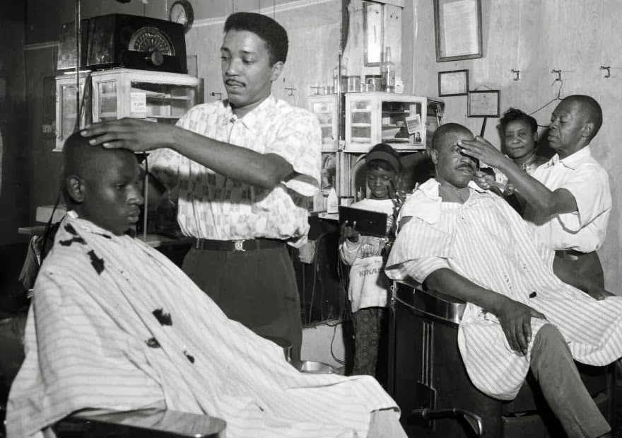 "Barbers Pete Boyd and Johnny Gator cut hair in Gator's barbershop circa 1950, while female relatives socialize in the background. Photo by Charles ""Teenie"" Harris, via the Carnegie Museum of Art."