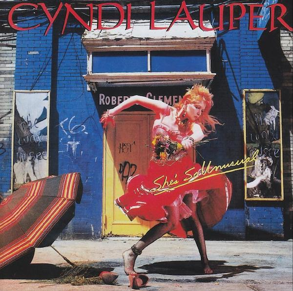 """Top: 1980s cartoon rock superstar Jem performs in a music video. (Via AnimationMagazine.com) Below: Jem-inspiration Cyndi Lauper on the cover of 1983's """"She's So Unusual,"""" the album that spawned the girl-power mega-hit, """"Girls Just Want to Have Fun."""""""