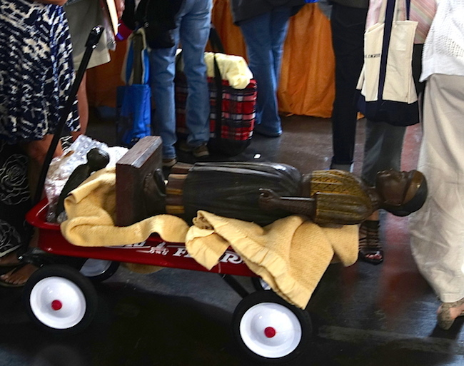 Large and small statues ride on a blanket in a Radio Flyer wagon as their owner waits in line.