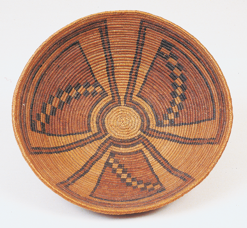 A 19th-century Pueblo tray from the Blaugrund collection. It coils left and features natural and dyed sumac sewing splints.