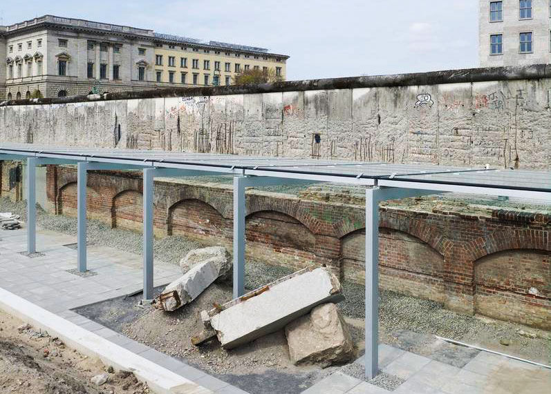 The degraded Berlin Wall rises behind the Topography of Terror, a memorial built around the subterranean ruins of the SS and Gestapo headquarters. (via Wiki Commons)