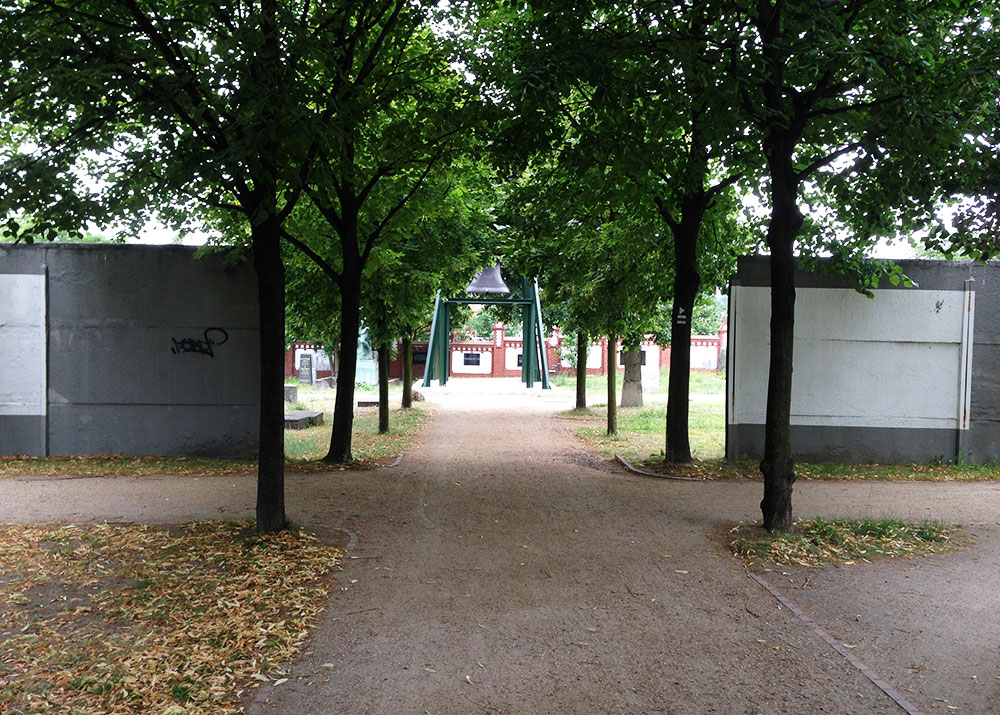 Two short segments of the Berlin Wall border fortifications flank pathways in Invalidenfriedhof, an 18th-century cemetery.
