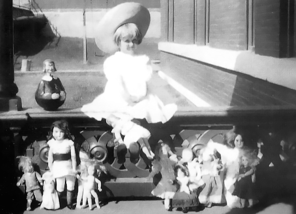 Huguette Clark poses with her dolls on the porch of the Clark mansion in Butte, Montana, circa 1910-11. (Via the collection of Paul Clark Newell, Jr., from EmptyMansionsBook.com)