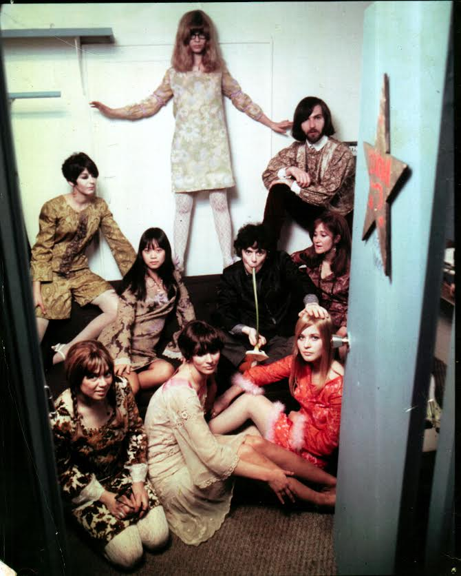 Trina Robbins (top) in Donovan's dressing room at The Trip, a club on the Sunset Strip in L.A., circa 1966. Everyone but Donovan (in the middle, sucking on a lily) is wearing clothes designed by Robbins. (Photo courtesy of Trina Robbins)