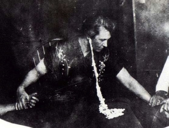 "Mina ""Margery"" Crandon excretes ""ectoplasm"" from her ear at a séance. (Via Mind-Energy.net)"