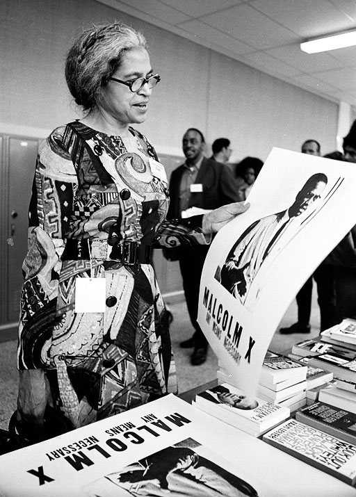 "LeRoy Henderson photographed Rosa Parks with a Malcolm X poster at the first National Black Political Convention in 1972. Courtesy <a href=""http://www.leroyhenderson.com/Welcome.html"">LeRoy Henderson</a>."