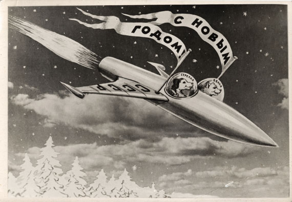 "A 1960 USSR postcard showing Belka and Strelka in their rocket by the photomontage artist Sveshnikov. The flags read, ""Happy New Year,"" the wing of the rocket reads, ""'USSR,"" and inside the cockpits, it says, ""Strelka"" and ""Belka."" (© FUEL Publishing)"