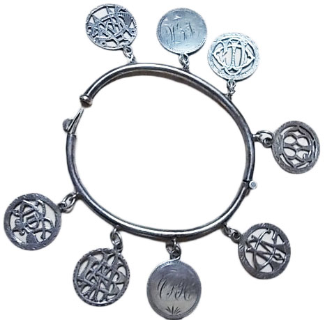 This silver hinged bangle features six love tokens with cut-out ovelapping initials and two with engraved  linear initials. (Courtesy of the Love Token Society)